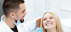A woman smiling at her dentist while he checks her cosmetic dental bonding
