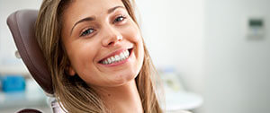Smiling woman in dental chair for preventive dentistry
