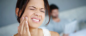 Woman in need of emergency dentistry holding jaw