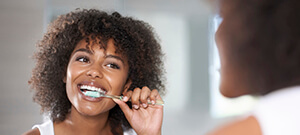 Woman brushing teeth as part of her preventive dentistry plan